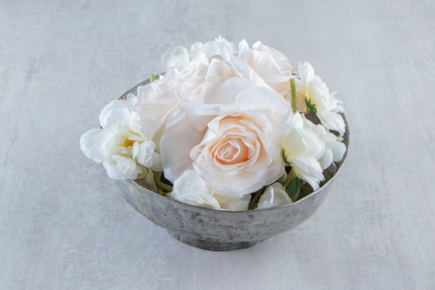 白いテーブルの上に、鉄のボウルに白いバラ。