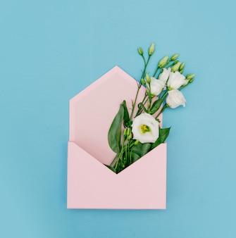 Белые розы в розовом конверте на синем фоне. вид сверху