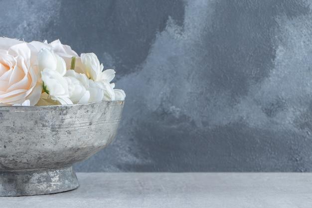 Rose bianche in una ciotola di ferro, su fondo bianco. Foto Gratuite