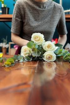 흰 장미는 나무 테이블에 놓여 있습니다. 플로리스트의 손이 꽃다발을 만들고 있습니다.