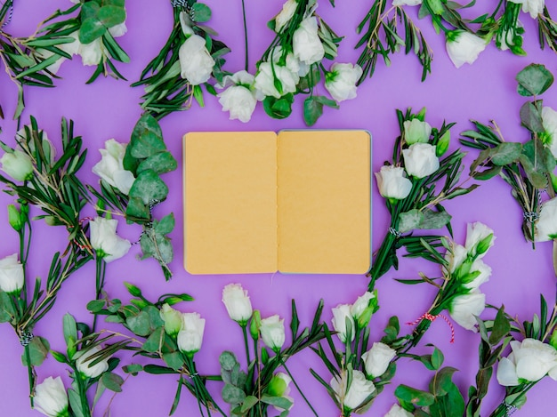 White roses and notebook recipe on purple background. above view