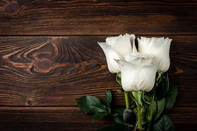 Белые розы на темном деревянном столе.