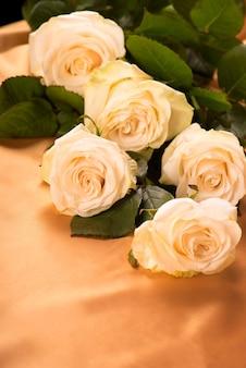 金色のシルクの背景に白いバラ