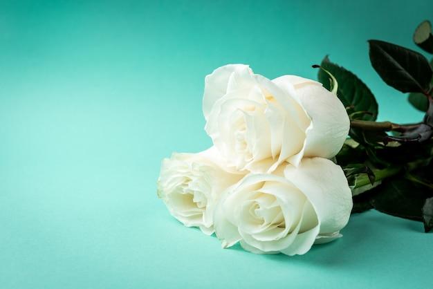 Белые розы на зеленом столе.