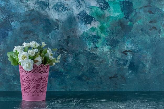 Rose bianche in un vaso di fiori rosa, su fondo bianco.