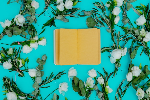 White roses and recipe notebook on green background. above view