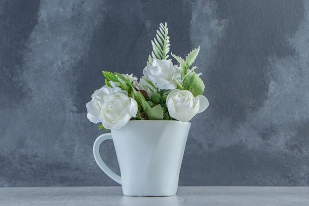 Rose bianche in una tazza bianca, su fondo bianco. foto di alta qualità