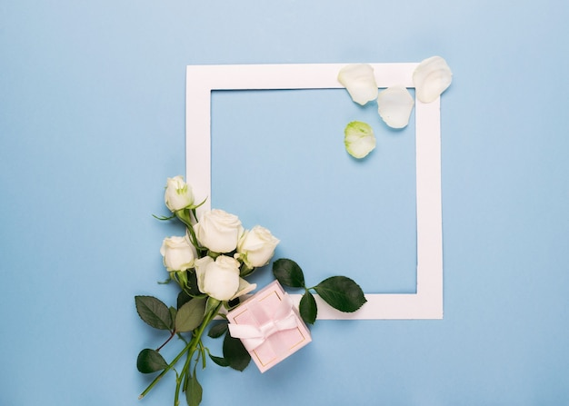 White roses and white frame present decorated with fresh leaves on a blue background