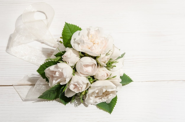 White roses on white table. top view
