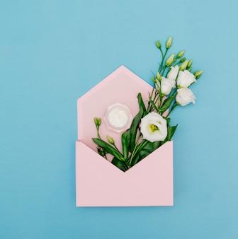 Белые розы со сливками в розовом конверте на синем фоне. вид сверху
