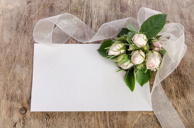 White roses with empty card on white table. top view