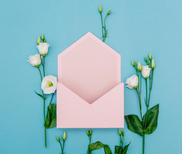 Белые розы с розовым конвертом на синем фоне. вид сверху