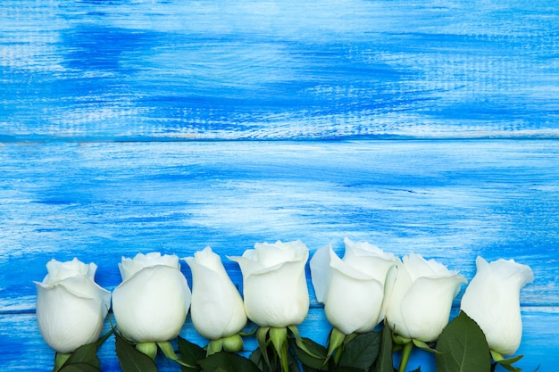 White roses on a wood background