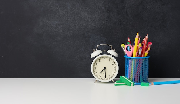 White round alarm clock and a metal glass with pens, pencils and felt-tip pens on the background of an empty black chalk board, copy space