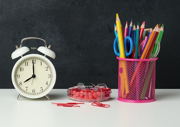 White round alarm clock and a metal glass with pens, pencils and felt-tip pens on the background of an empty black chalk board