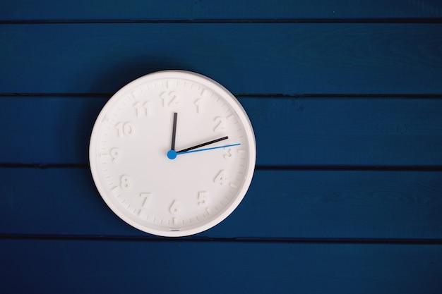 White round clock is on dark blue wooden wall