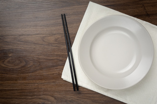 A white round empty plates and chopstick on wooden table