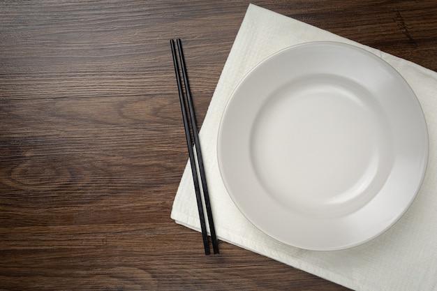 Piatti vuoti rotondi bianchi e bacchette sulla tavola di legno