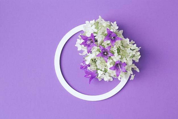 Белая круглая рамка с белыми и фиолетовыми цветами на сиреневом фоне. плоская планировка. минималистичная летне-весенняя композиция