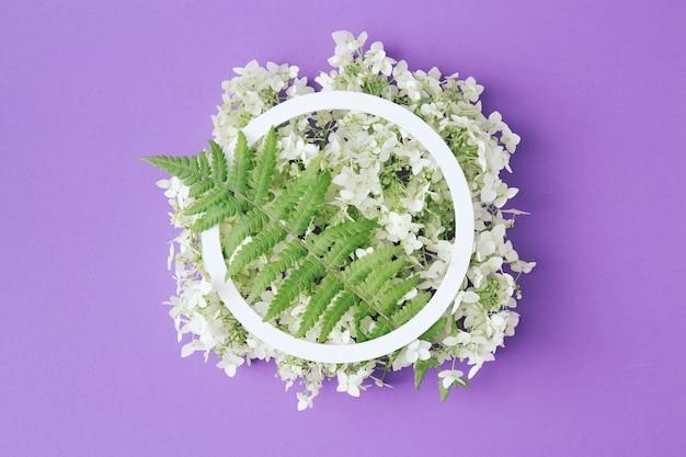 Белая круглая рамка с белыми цветами и зелеными листьями на сиреневом фоне. плоская планировка. минималистичная летне-весенняя композиция.