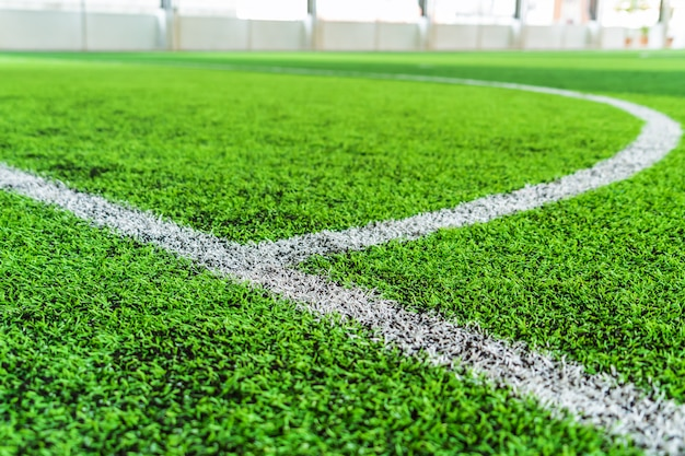 White round goal line on green grass for sport soccer field with nobody
