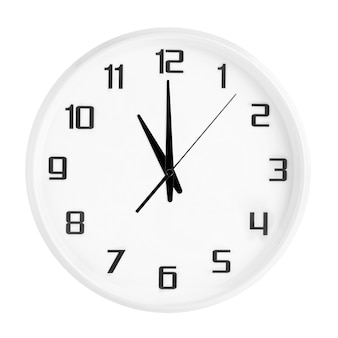 White round office clock showing eleven o'clock isolated on white.