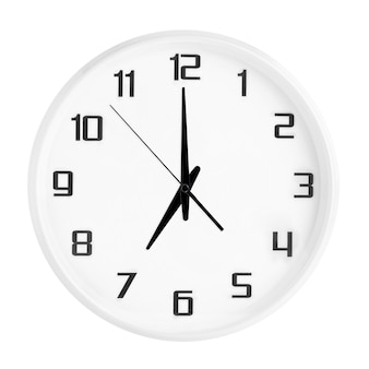 White round office clock showing seven o'clock isolated on white. blank white clock showing 7 pm or 7 am time