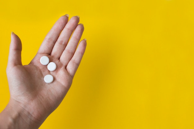 White round pills in female hand on yellow  with copy space