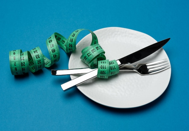 White round plate and fork and knife wrapped in green measuring tape on blue background, weight loss concept, flat lay