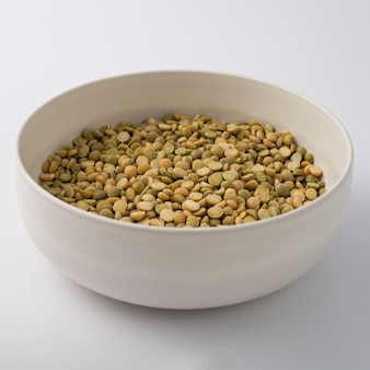 未調理の緑のレンズ豆でいっぱいの白い丸いプレート。白で隔離。