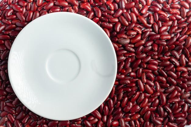 Место белой круглой тарелки среди красной фасоли