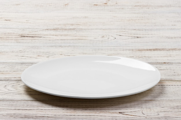 White round plate on white wooden table background. perspective view