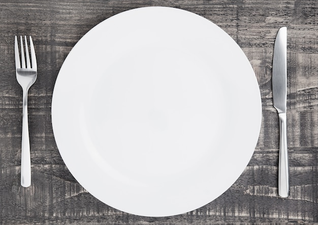 White round plate with fork and knife on wooden board surface