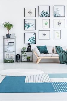Белый круглый ковер и синий ковер с полосами на полу в интерьере светлой гостиной с деревянным диваном, металлическими стеллажами с растениями и плакатами, висящими на стене