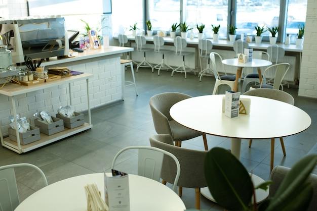 Белые круглые столы в окружении удобных кресел и стульев вдоль окна в уютном кафе