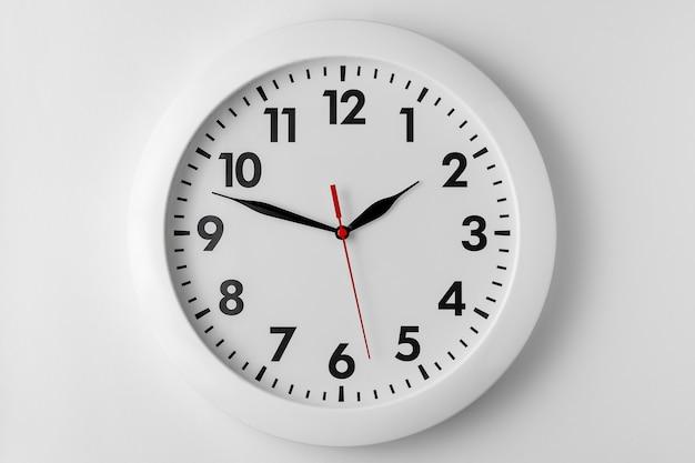 明るい灰色の背景、自然な影に分離された白い丸い壁時計