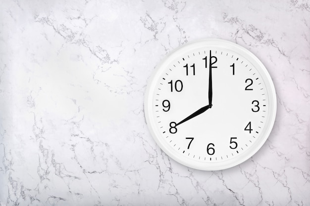 White round wall clock on marble background. eight o'clock.