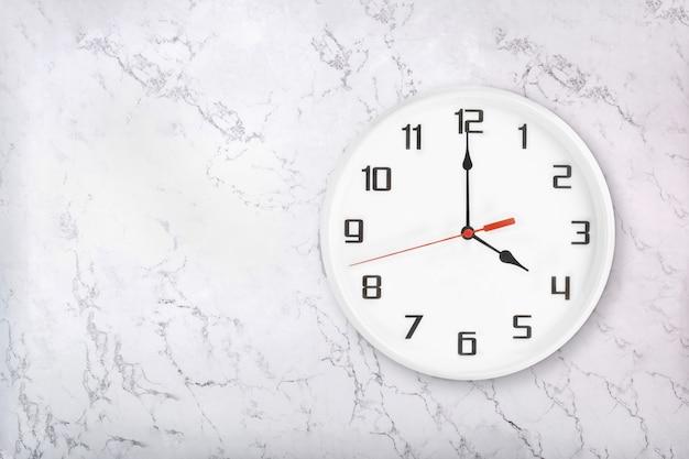 Белые круглые настенные часы на белой естественной мраморной предпосылке. четыре часа