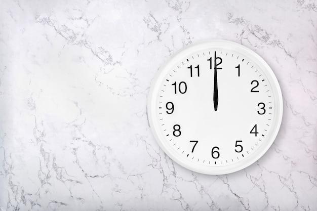 白い天然大理石の背景に白い丸い壁時計。正午