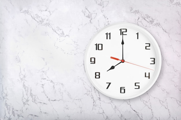 White round wall clock on white natural marble background. eight o'clock
