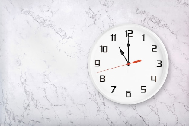 White round wall clock on white natural marble background. eleven o'clock