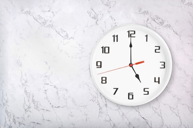 White round wall clock on white natural marble background. five o'clock