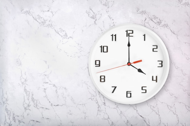 White round wall clock on white natural marble background. four o'clock