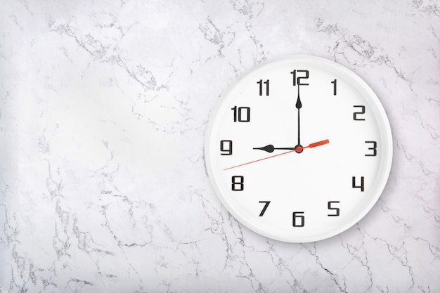 White round wall clock on white natural marble background. nine o'clock