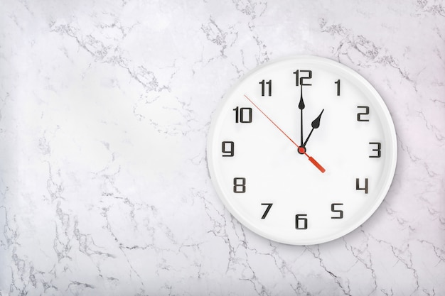 White round wall clock on white natural marble background. one o'clock