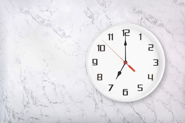 White round wall clock on white natural marble background. seven o'clock