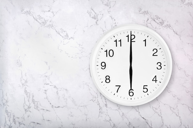 White round wall clock on white natural marble background. six o'clock.