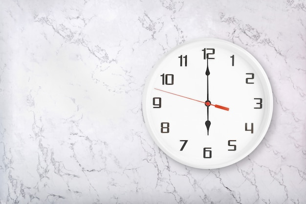 White round wall clock on white natural marble background. six o'clock