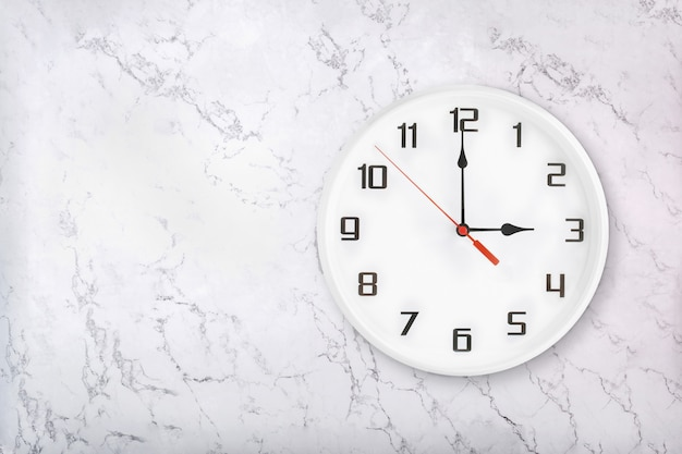 White round wall clock on white natural marble background. three o'clock
