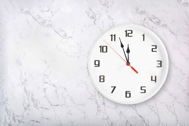 White round wall clock on white natural marble background.